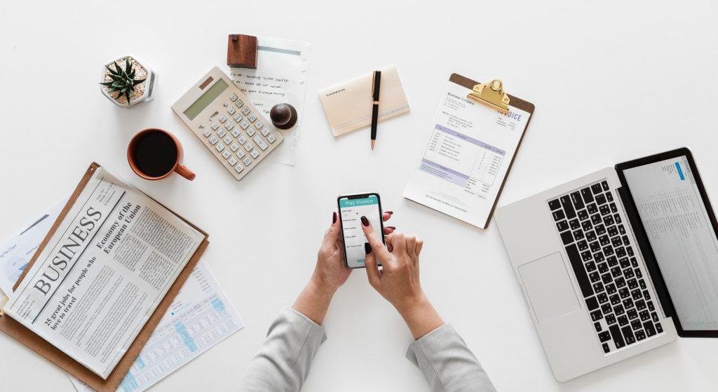Recepcionista de oficina virtual utilizando su smartphone en un escritorio de trabajo